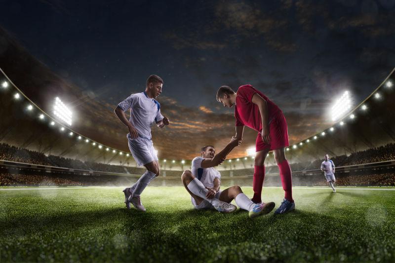 夜空下的足球场上帮助跌倒的运动员