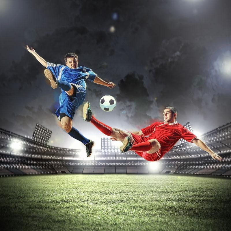 夜晚的足球场上两个穿着红色和蓝色运动服的足球运动员在踢足球