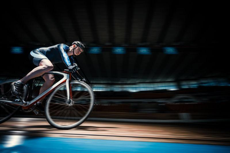黑色背景下骑自行车的运动员