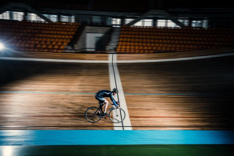在有观众席的体育场骑自行车的赛车手