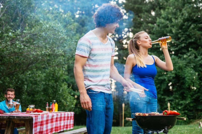 年轻的夫妻俩边喝啤酒边烧烤