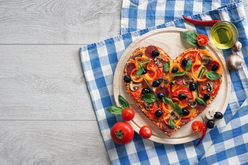 白色木桌上的心形披萨饼