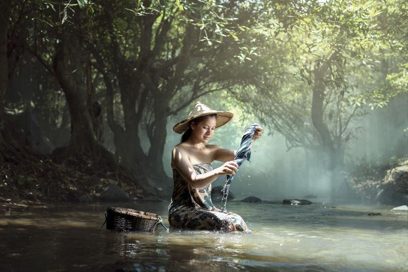 女人在小河上洗衣服