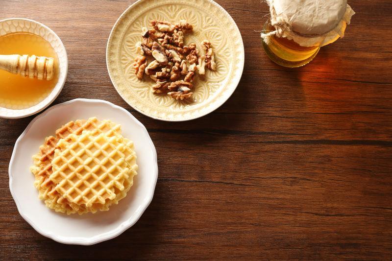 木桌上新鲜的蜂蜜华夫饼和核桃