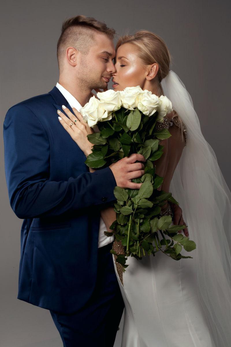 灰色背景下穿着婚纱的新娘和帅气的新郎