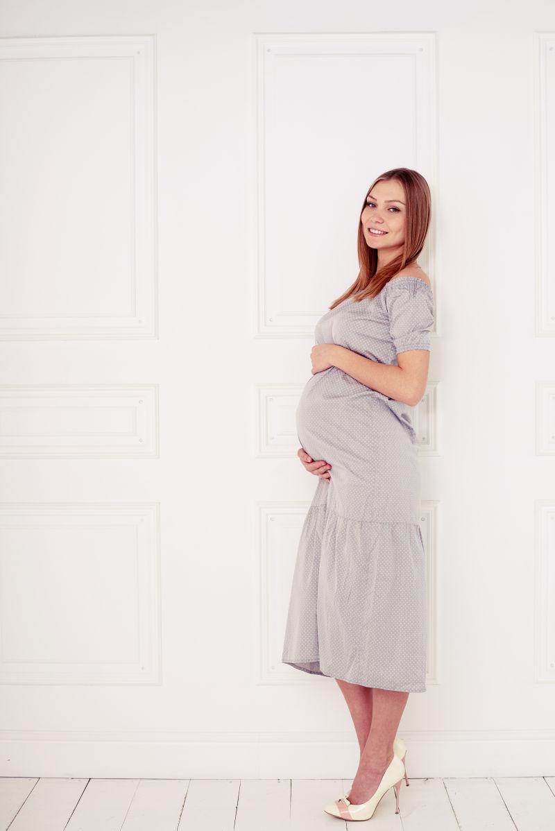 穿着灰色裙子靠在墙边的孕妇