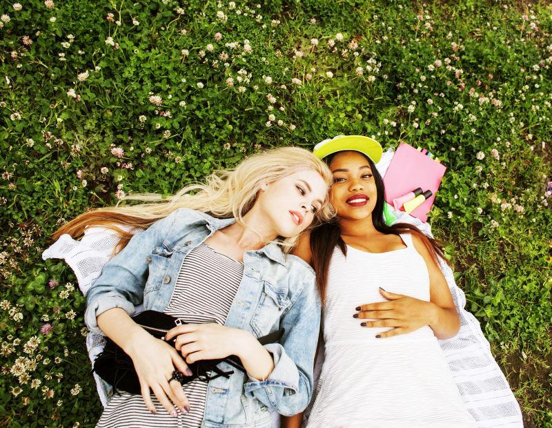 两个漂亮的女孩在草地上开心地玩耍