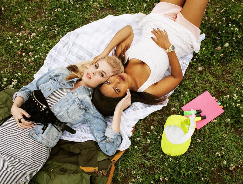 两个漂亮的女孩在草地上开心地笑