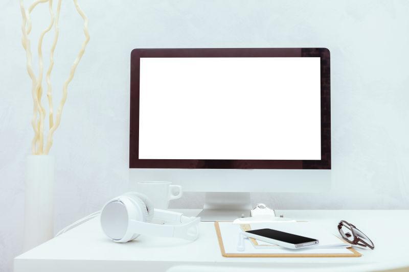 白色办公桌上的苹果电脑还有各种数码产品