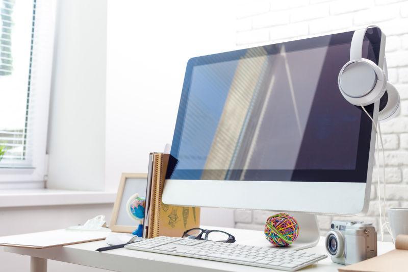 窗户边的办公桌上有一台苹果电脑挂着白色耳机