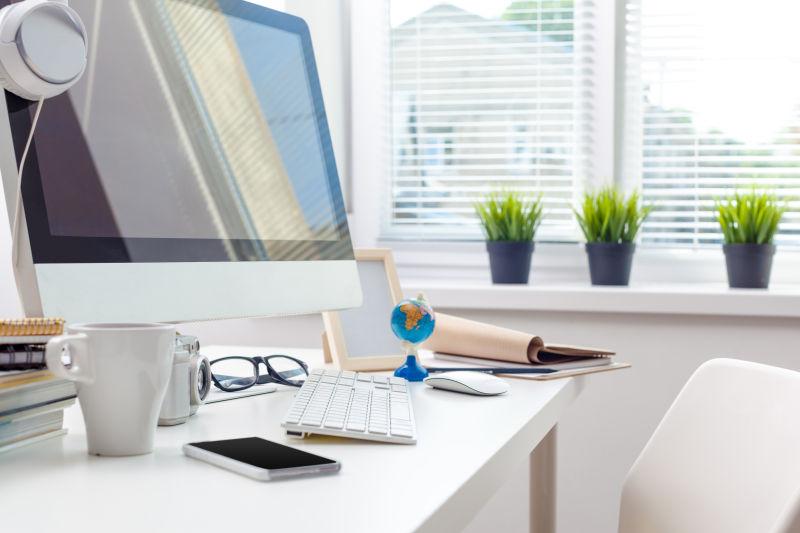 办公室白色办公桌上的苹果电脑和各种办公用品