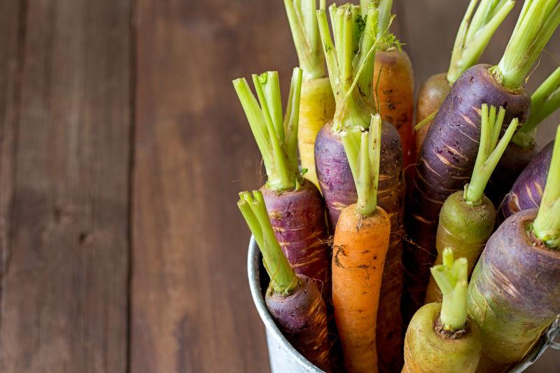 木板上堆放在桶里的胡萝卜