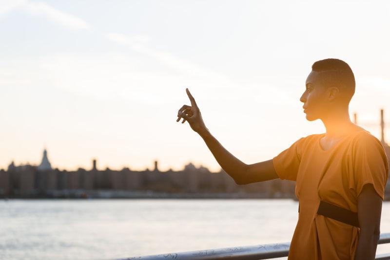 黑人女子指着城市风景