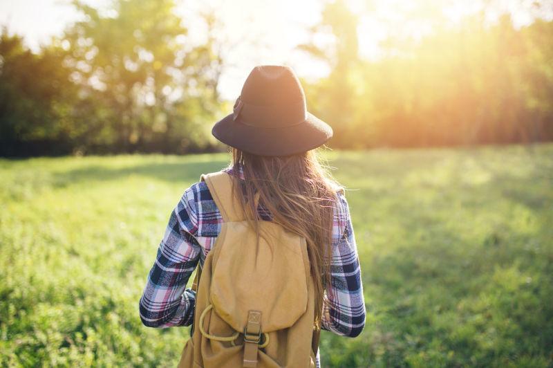 美女在公园草地上行走的背影