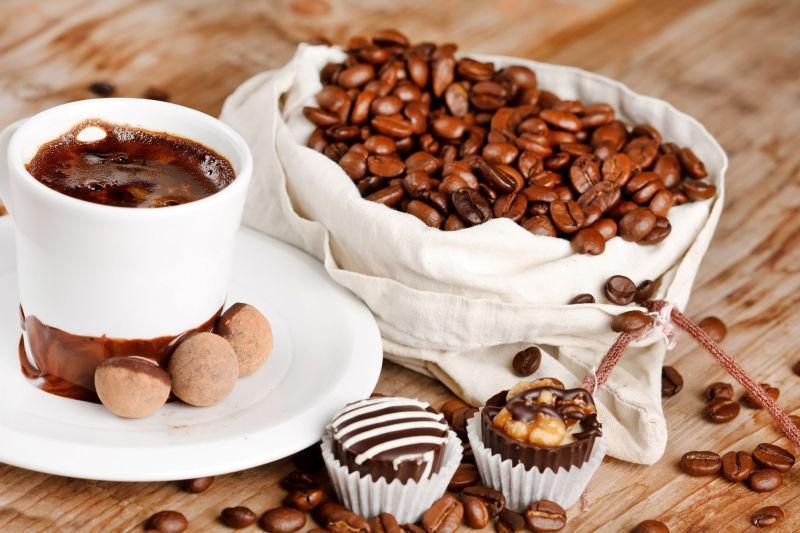 木桌上的咖啡豆和一杯咖啡以及甜点