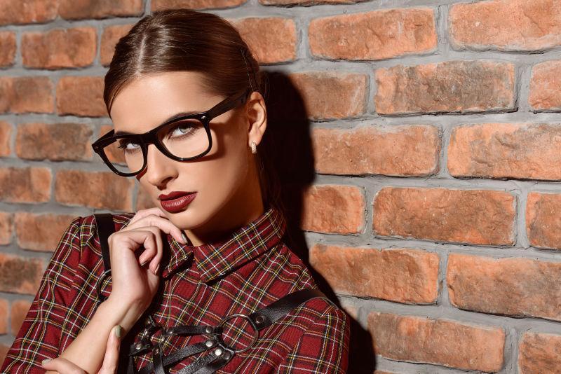砖墙边的穿着格子裙子戴眼镜的美女