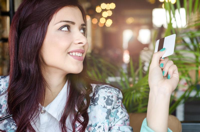 年轻女士在餐厅用信用卡付账