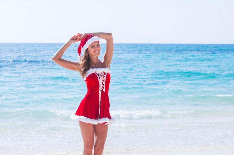 圣诞假期在热带海滩上身穿克劳斯夫人的服装的美丽女人