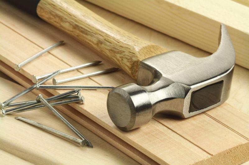 木板上崭新的锤子和钉子
