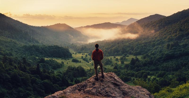 夕阳下站在悬崖峭壁上欣赏自然风光的年轻人