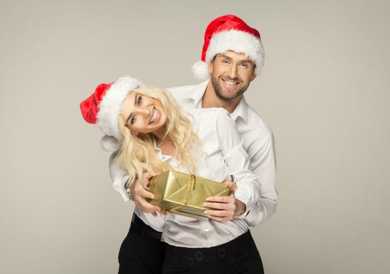 拿着圣诞礼物盒的恩爱夫妻