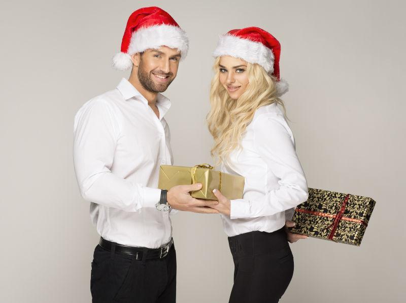带着圣诞帽的外国夫妻在互换礼物