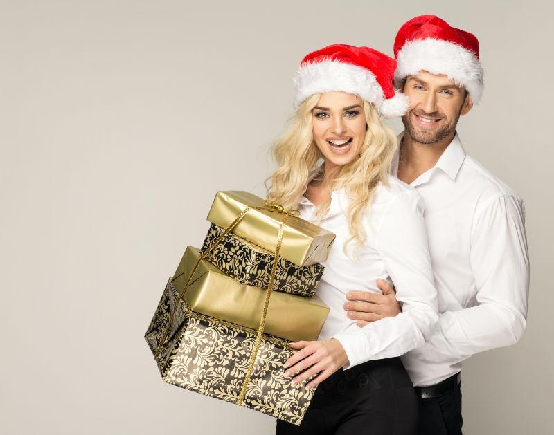 带着红色圣诞帽的夫妻端着一堆圣诞礼物