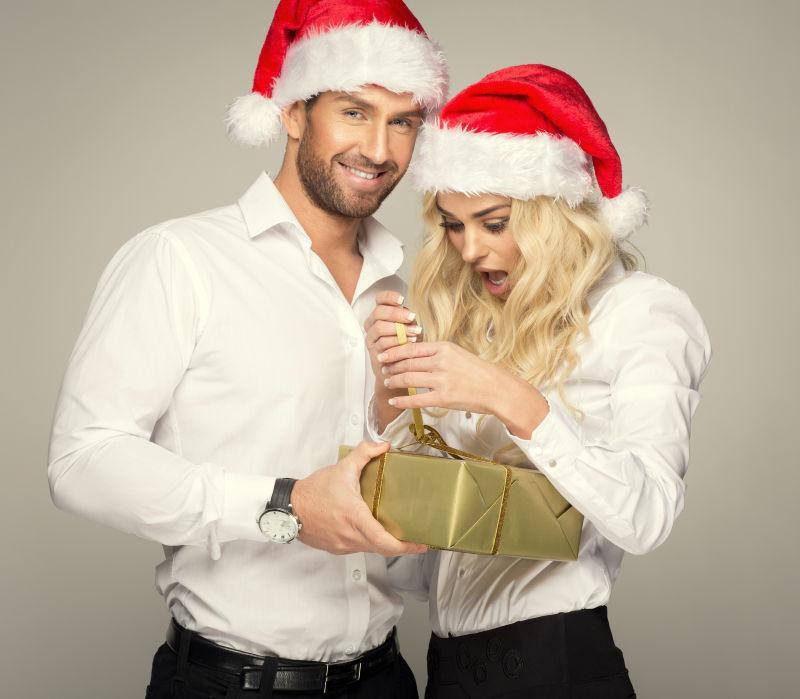 带着圣诞帽的夫妻在拆圣诞礼物