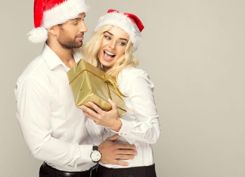 时尚的外国夫妻拿着礼物盒带着红色的圣诞帽子
