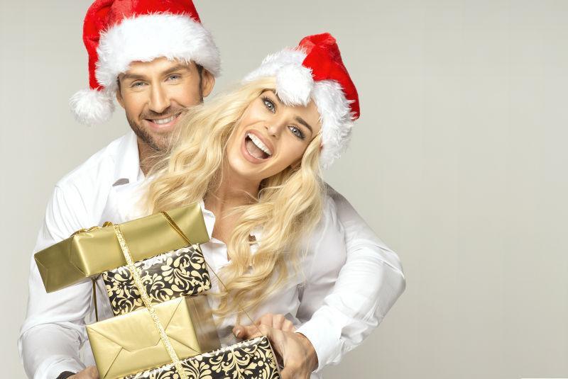 带着红色圣诞帽的外国夫妻端着四个礼物盒子
