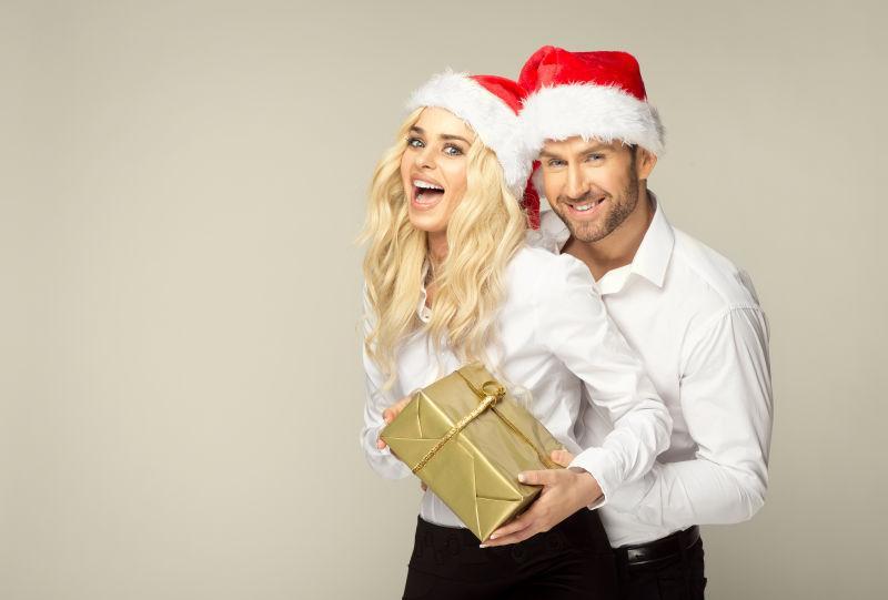 带着圣诞帽子的夫妻拿着金色的礼物盒