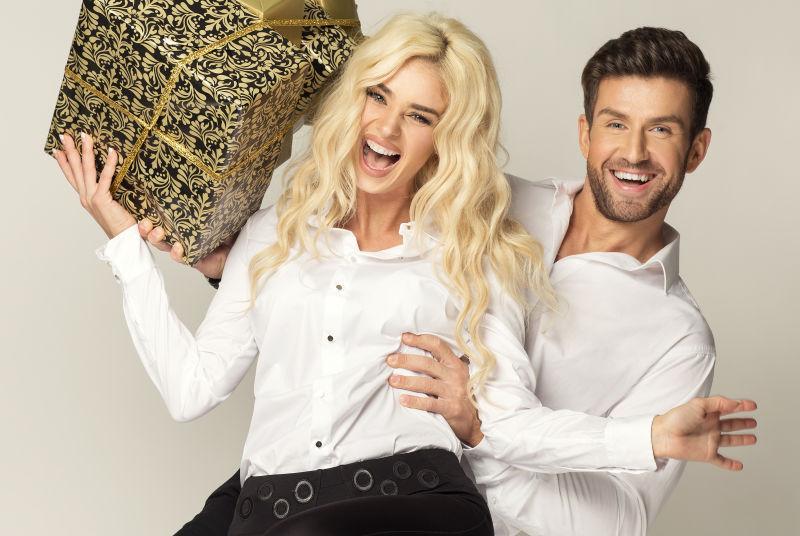 时尚的外国夫妻拿着礼物盒