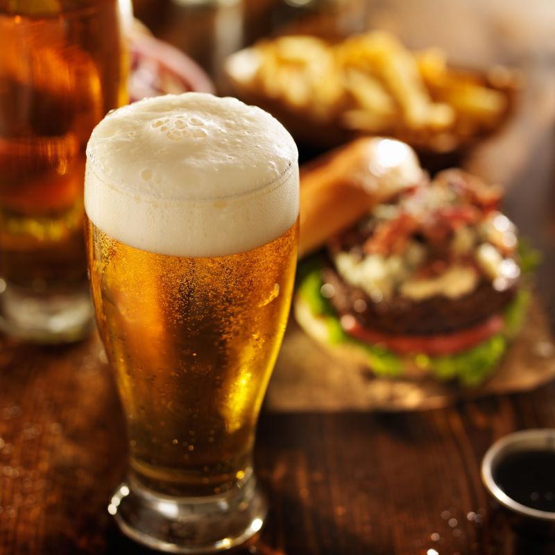餐桌上的汉堡包和一杯满满的啤酒