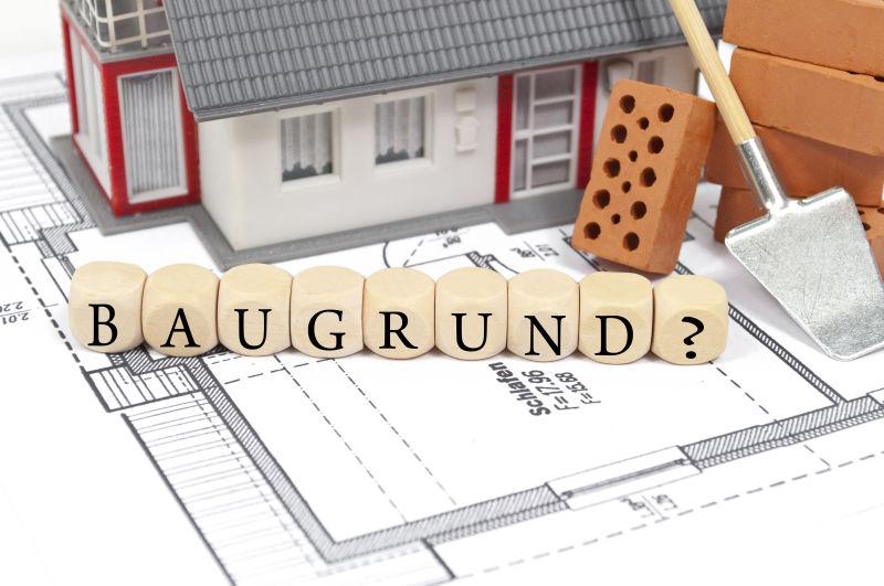 白色图纸上的岩土工程建设砖和房屋模型