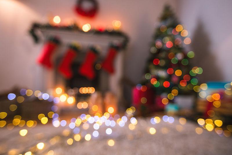 起居室家中圣诞树灯和壁炉的散焦