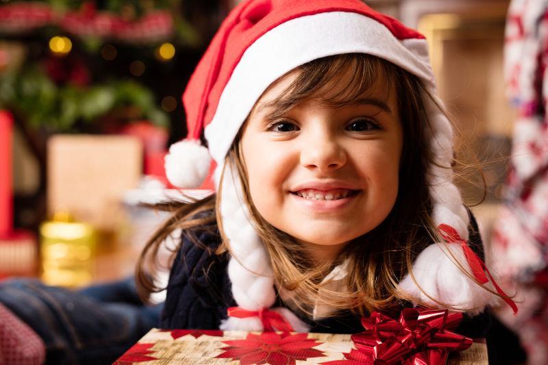 拿着圣诞节礼物戴着圣诞帽的女孩