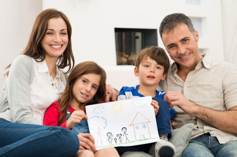 在沙发上举着一幅画的幸福四口之家