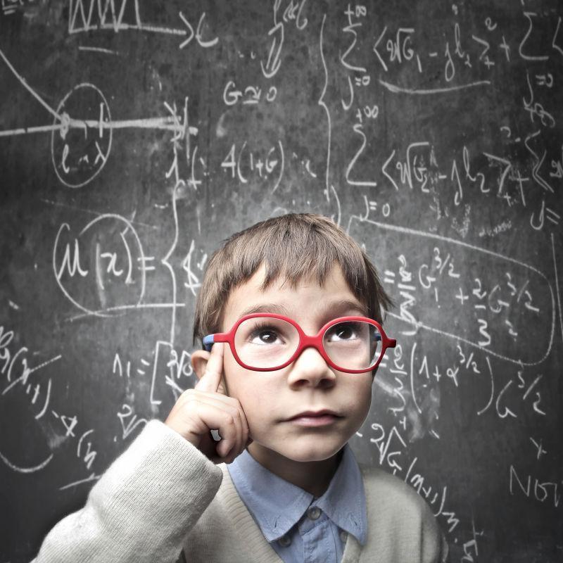 在黑板前思考的金发男孩