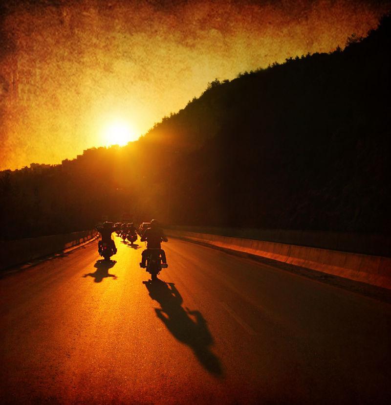 日落时分街道上骑摩托车的人