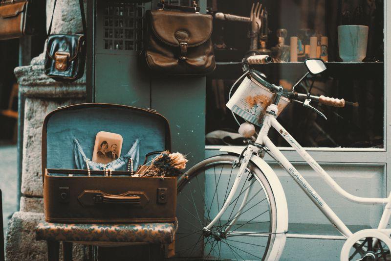 停靠在路边的白色自行车和旁边的箱子