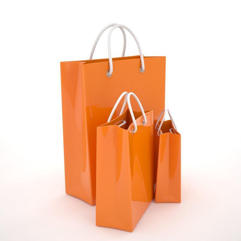 白色背景下的不同大小的橙色纸质购物袋