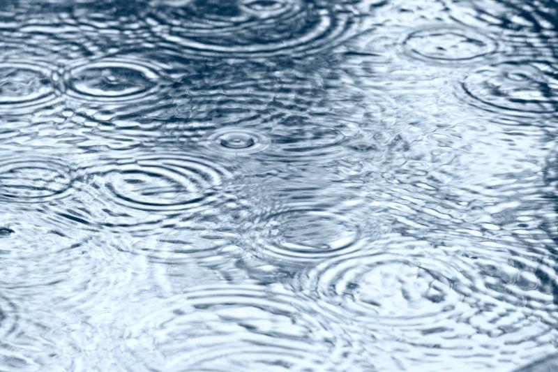 雨水落在水坑上溅射起来的美丽水花