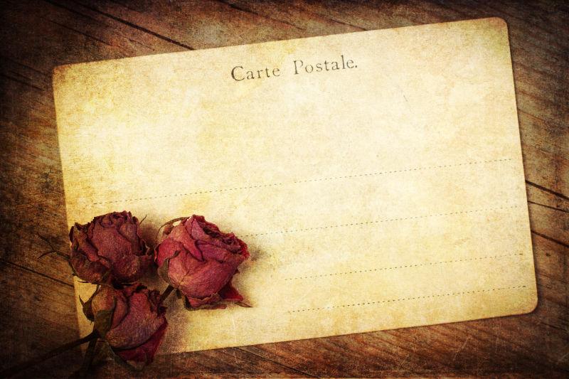 木制背景下的旧玫瑰明信片
