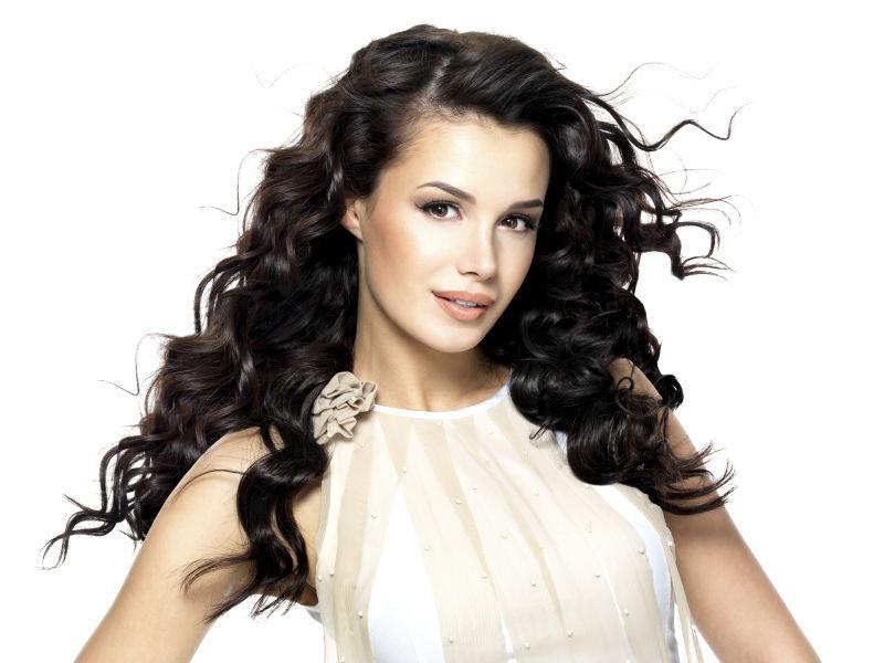 在白色背景下长着美丽的黑色波浪卷发的时尚美女模特