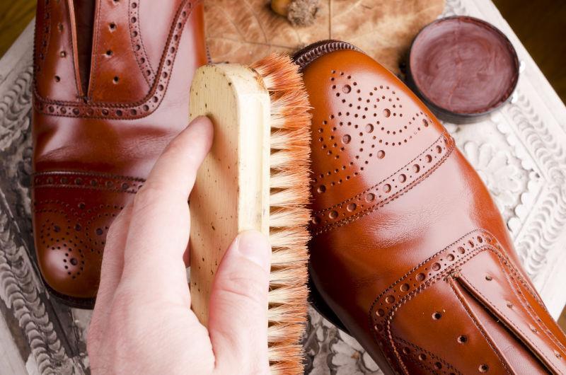 鞋匠指修理鞋子的手和带抛光设备的棕色皮鞋