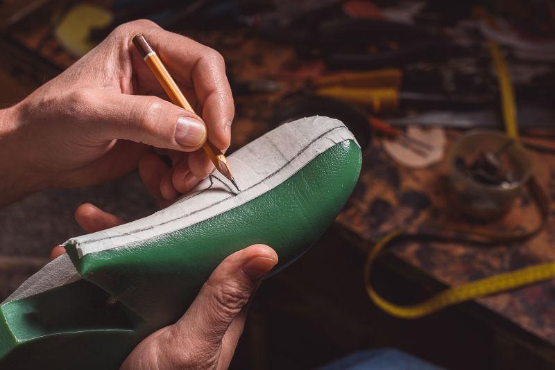 鞋匠在塑料垫上设计鞋子