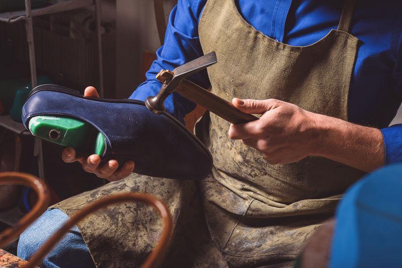拿着靴子和锤子的鞋匠