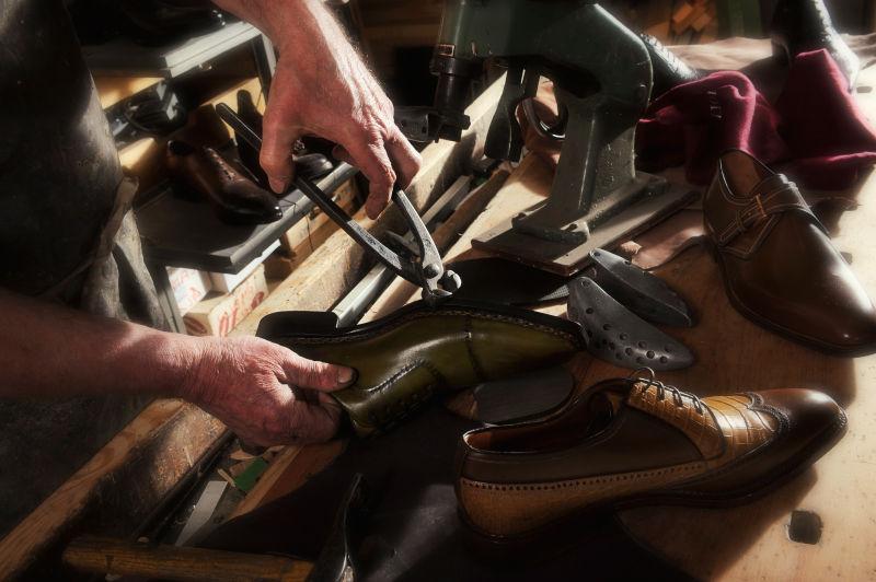 鞋匠拿着工具制作鞋子