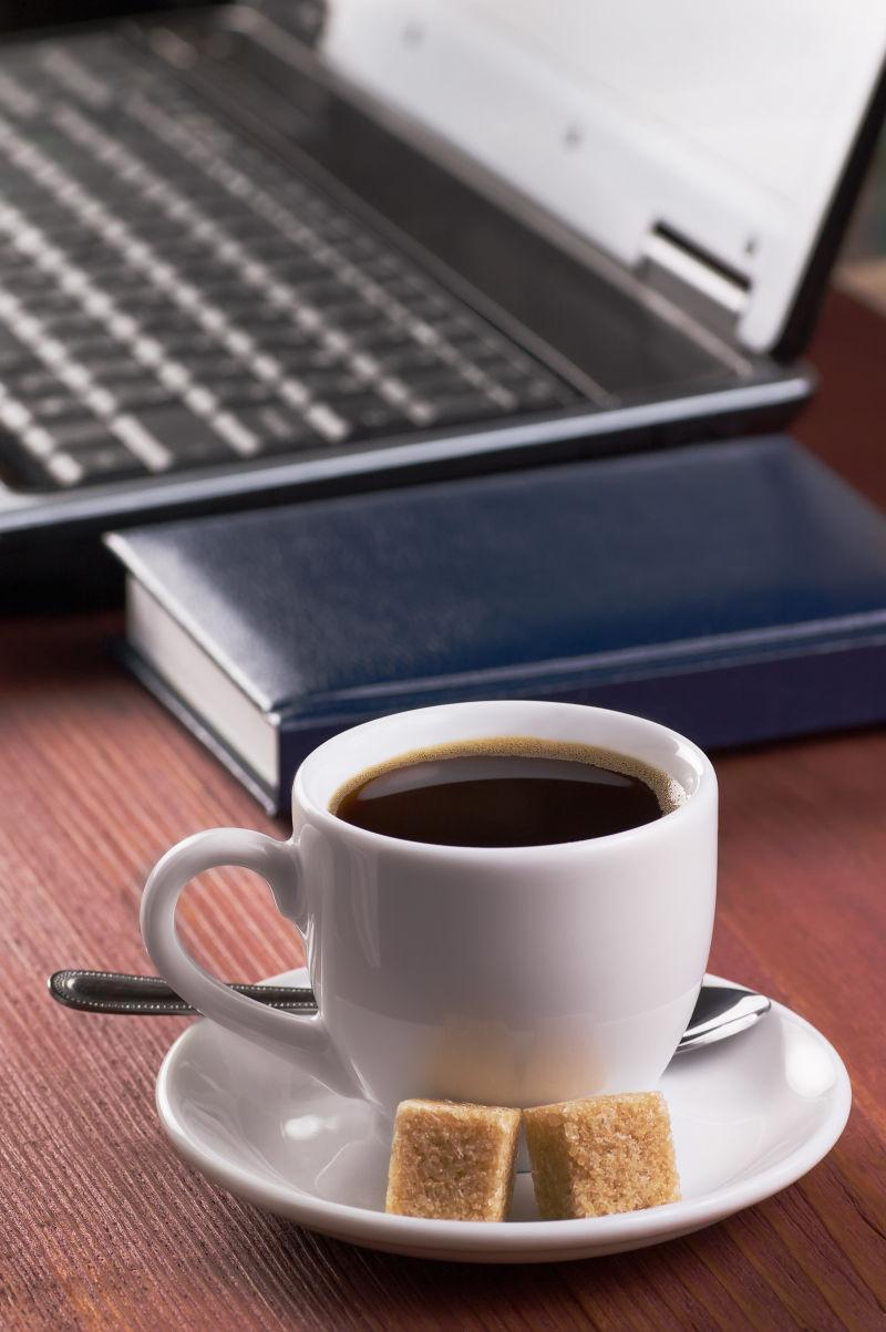 木桌上笔记本电脑旁边的一杯咖啡