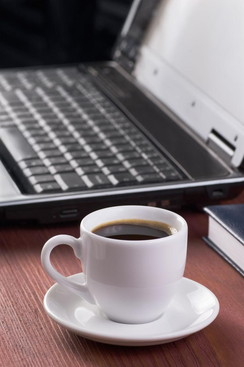 木纹理桌上的笔记本电脑旁边的一杯咖啡